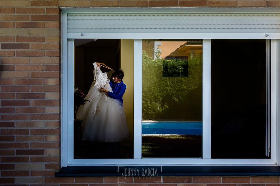 Boda en el Castillo de las Seguras de Cáceres de Marta y Charley realizada por Johnny García, fotógrafo de bodas en Cáceres. La madre de Marta prepara el vestido.