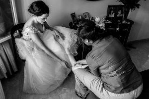 Boda en el Castillo de las Seguras de Cáceres de Marta y Charley realizada por Johnny García, fotógrafo de bodas en Cáceres. La madre de Marta la ayuda con los zapatos.