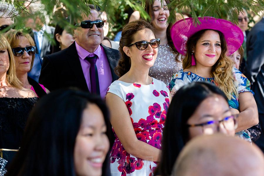 Boda en el Castillo de las Seguras de Cáceres de Marta y Charley realizada por Johnny García, fotógrafo de bodas en Cáceres. Invitadas sonrien en la ceremonia.