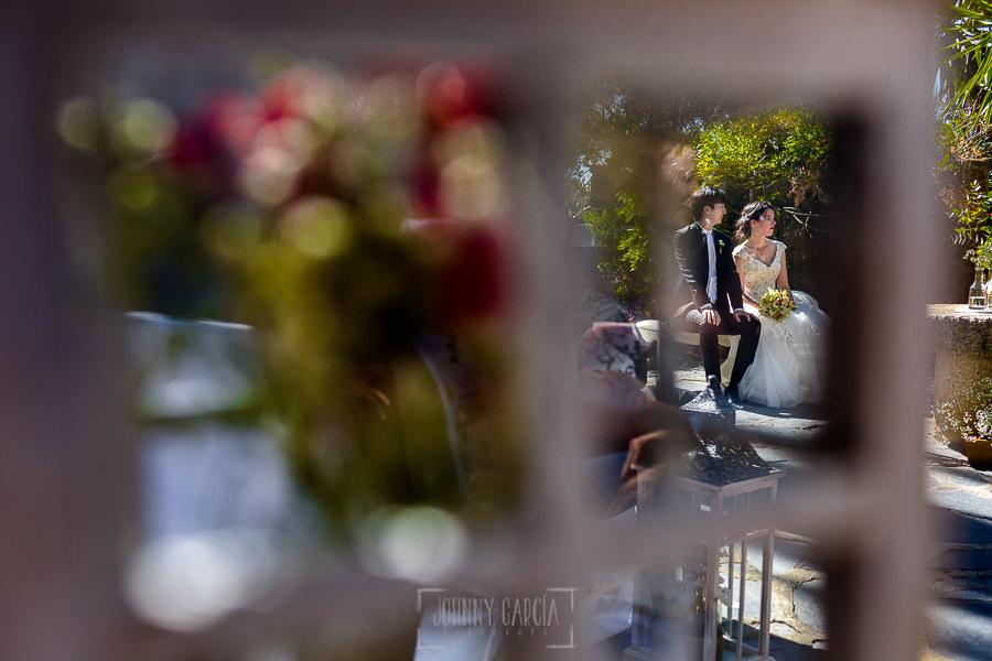 Boda en el Castillo de las Seguras de Cáceres de Marta y Charley realizada por Johnny García, fotógrafo de bodas en Cáceres. Los novios a través de la ventana de un farol.