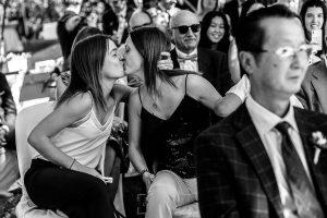 Boda en el Castillo de las Seguras de Cáceres de Marta y Charley realizada por Johnny García, fotógrafo de bodas en Cáceres. Invitadas se besan en la ceremonia.