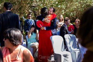 Boda en el Castillo de las Seguras de Cáceres de Marta y Charley realizada por Johnny García, fotógrafo de bodas en Cáceres. Invitados se abrazan en la ceremonia.