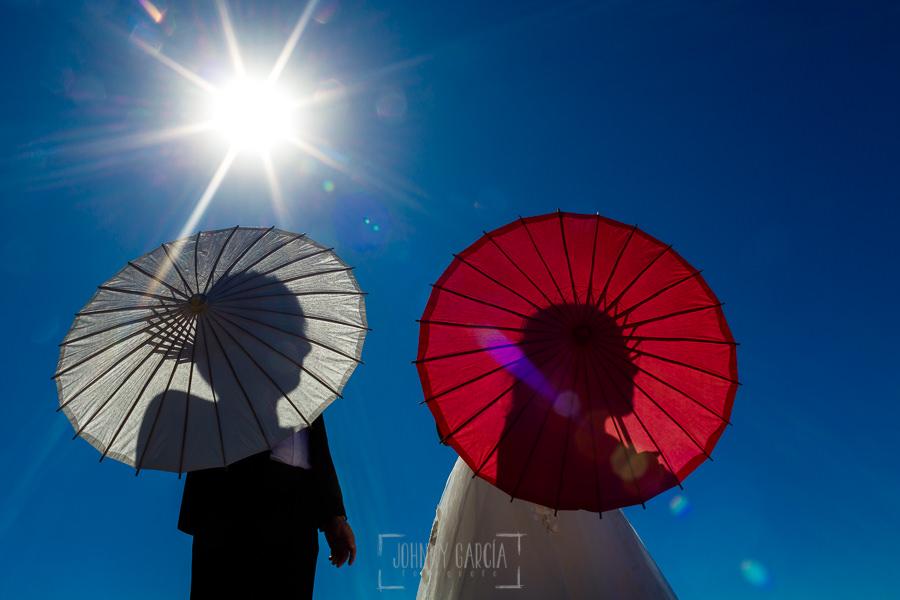 Boda en el Castillo de las Seguras de Cáceres de Marta y Charley realizada por Johnny García, fotógrafo de bodas en Cáceres. Retrato de la pareja con unos paraguas chinos.