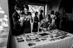 Boda en el Castillo de las Seguras de Cáceres de Marta y Charley realizada por Johnny García, fotógrafo de bodas en Cáceres. Los novios miran unas fotos de grupo.