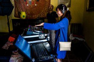 Boda en el Castillo de las Seguras de Cáceres de Marta y Charley realizada por Johnny García, fotógrafo de bodas en Cáceres. Una invitada pone música en la fiesta.