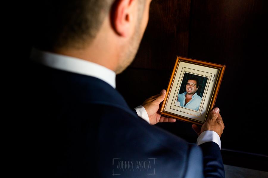 Boda en Hacienda de Regla, Sevilla, de Jessica y Sergio, Johnny García, fotógrafo de bodas en Sevilla; Sergio mira la fotografía de su padre fallecido.