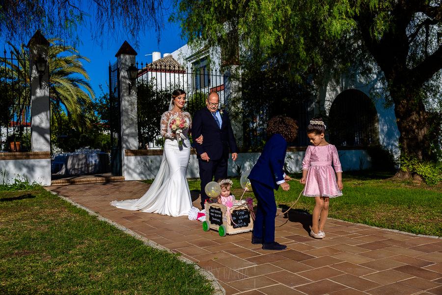 Boda en Hacienda de Regla, Sevilla, de Jessica y Sergio, Johnny García, fotógrafo de bodas en Sevilla; la novia del brazo del padrino camino del altar.