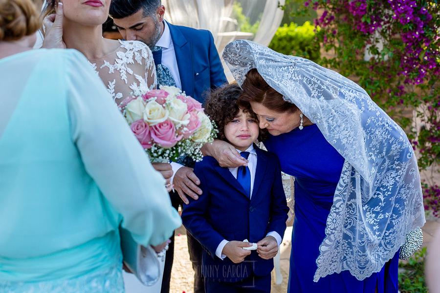 Boda en Hacienda de Regla, Sevilla, de Jessica y Sergio, Johnny García, fotógrafo de bodas en Sevilla; la madrina consuela al hijo del novio emocionado.
