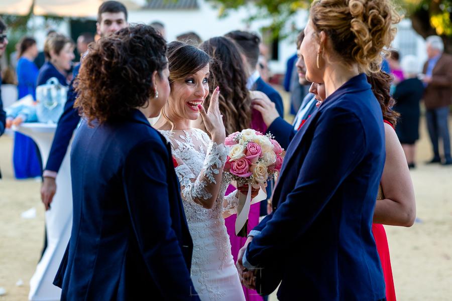 Boda en Hacienda de Regla, Sevilla, de Jessica y Sergio, Johnny García, fotógrafo de bodas en Sevilla; la novia enseña la alianza a sus amigas.