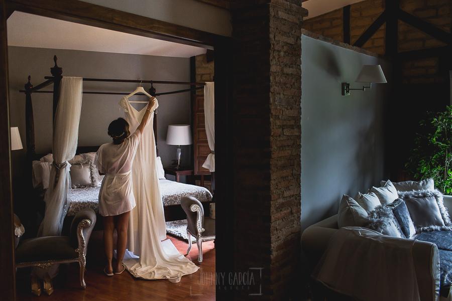 Boda hotel Ruta Imperial de Sandra y David realizada por el fotógrafo de bodas en Jarandilla de la Vera Johnny García, Sandra coloca su vestido.