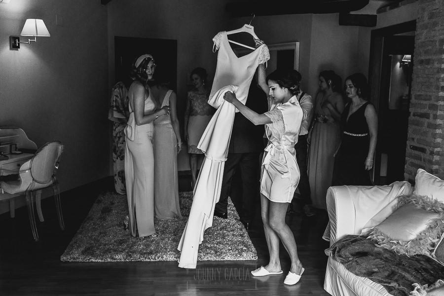 Boda hotel Ruta Imperial de Sandra y David realizada por el fotógrafo de bodas en Jarandilla de la Vera Johnny García, Sandra coge el vestido de novia.