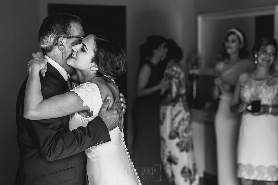 Boda hotel Ruta Imperial de Sandra y David realizada por el fotógrafo de bodas en Jarandilla de la Vera Johnny García, Sandra abraza al padrino