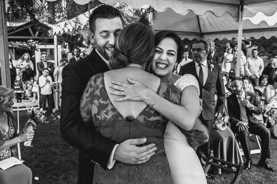 Boda hotel Ruta Imperial de Sandra y David realizada por el fotógrafo de bodas en Jarandilla de la Vera Johnny García, la pareja abraza a la maestra de ceremonia