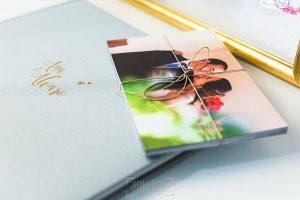 Libro de boda serie editorial en lino gris con el sello de la pareja grabado en láser junto a unas copias en papel.