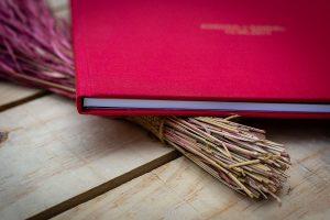 Libro de boda serie editorial en rojo con los nombres de la pareja grabado en láser con el nombre de los novios grabados en oro, detalle del lateral.