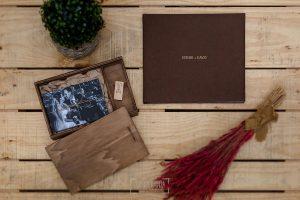 Libro de boda serie editorial en lino marrón con el sello de la pareja grabado en láser con el nombre de los novios grabados en láser, el libro junto a una caja de madera con fotos en papel.