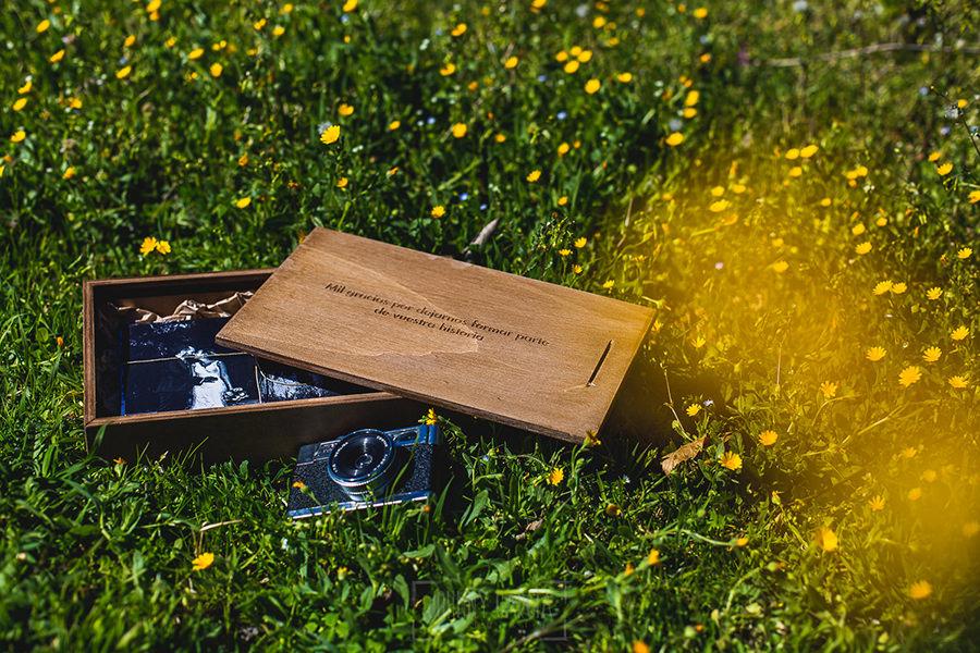 Una caja de madera con fotos en papel impresas como postales.