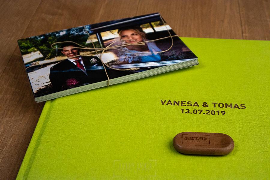 Libro de boda serie editorial en lino verde manzana con el sello de la pareja grabado en láser con el nombre de los novios grabados en láser, junto al pendrive y unas copias de papel.