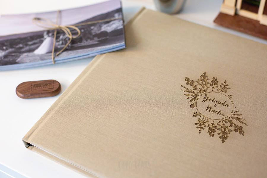 Álbum de boda serie editorial en lino arena con el sello de la pareja grabado en láser, detalle del libro junto a unas copias en papel y el pendrive grabado.