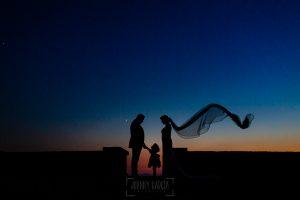 Boda en La Alberca de Sonia y Juanjo realizada por el fotógrafo de bodas en Salamanca Johnny García. Foto de la sesión de postboda a contraluz de los novios con su hija en la puesta de sol.