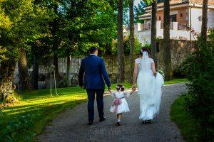 Boda en La Alberca de Sonia y Juanjo realizada por el fotógrafo de bodas en Salamanca Johnny García. Los novios con su hija caminan de espalda.