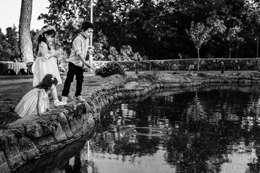 Boda en La Alberca de Sonia y Juanjo realizada por el fotógrafo de bodas en Salamanca Johnny García. un grupo de peques arrojan piedras al lago.