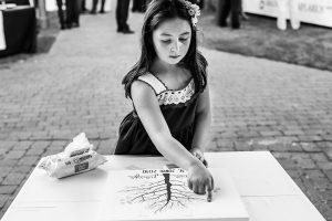 Boda en La Alberca de Sonia y Juanjo realizada por el fotógrafo de bodas en Salamanca Johnny García. Una niña pone su huella en un lienzo.