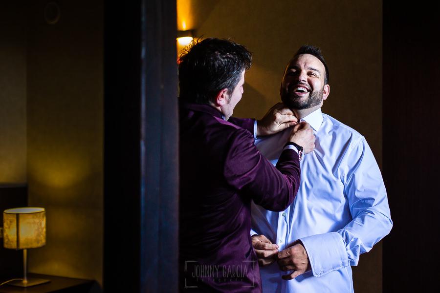 Boda en La Alberca de Sonia y Juanjo realizada por el fotógrafo de bodas en Salamanca Johnny García. El amigo de juanjo le abrocha el botón del cuello.