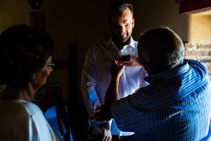 Boda en Béjar de Vanessa y Jorge realizada por Johnny García, fotógrafo de bodas en Béjar. Los padres de Jorge le ayudan a vestirse.
