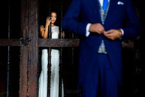 Bodas en Piedrahíta de Ana y Alberto, realizada por el fotógrafo de bodas en Salamanca Johnny García. Ana detras de una puerta de la iglesia.