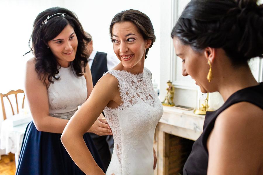 Bodas en Piedrahíta de Ana y Alberto, realizada por el fotógrafo de bodas en Salamanca Johnny García. Las amigas la ayudan con los botones del vestido.