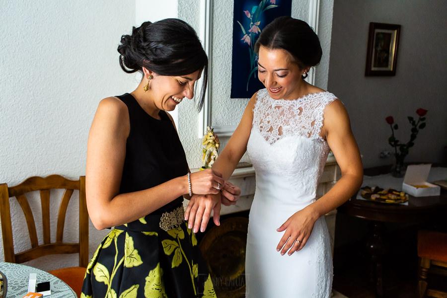 Bodas en Piedrahíta de Ana y Alberto, realizada por el fotógrafo de bodas en Salamanca Johnny García. Una amiga le ayuda con una pulsera.