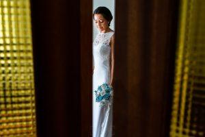 Bodas en Piedrahíta de Ana y Alberto, realizada por el fotógrafo de bodas en Salamanca Johnny García. Una foto de Ana a través del hueco de la puerta.