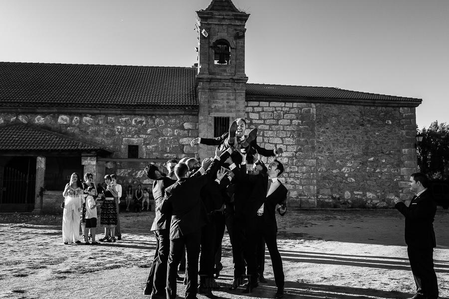 Bodas en Piedrahíta de Ana y Alberto, realizada por el fotógrafo de bodas en Salamanca Johnny García. Los amigos del novio le mantean en la puerta de la ermita.