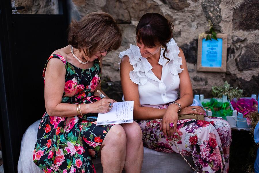 Bodas en Piedrahíta de Ana y Alberto, realizada por el fotógrafo de bodas en Salamanca Johnny García. Dos invitadas firman en el libro de firmas.