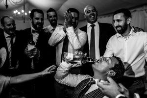 Bodas en Piedrahíta de Ana y Alberto, realizada por el fotógrafo de bodas en Salamanca Johnny García. Un hermano de Alberto bebe de una botella que llevan los amigos.