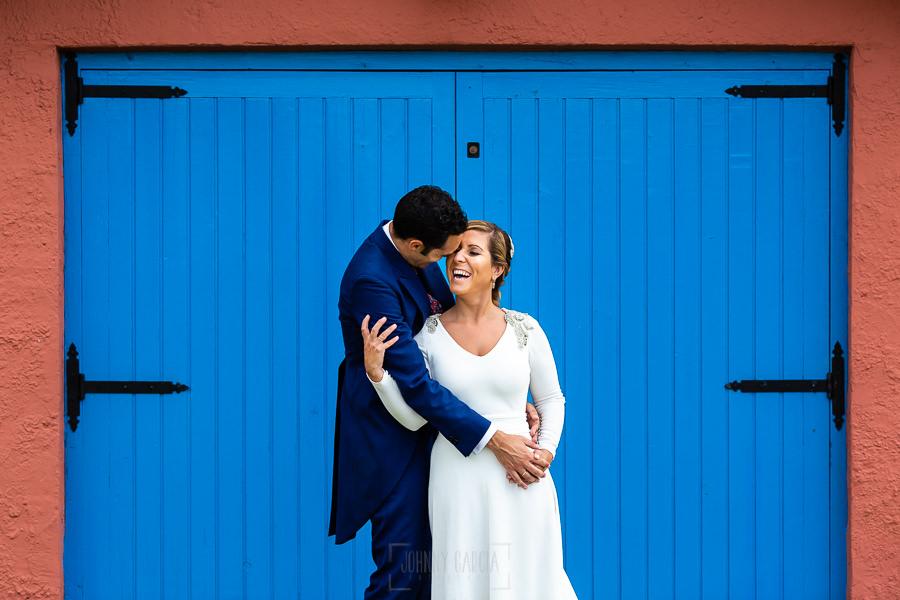 Boda en Villaviciosa de Carmen y David realizada por el fotógrafo de bodas en Asturias Johnny García. Foto de postboda, la pareja delante de una puerta azul.