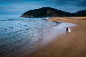Boda en Villaviciosa de Carmen y David realizada por el fotógrafo de bodas en Asturias Johnny García. Foto de postboda, la pareja pasea por la playa de Rodiles.