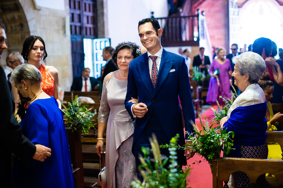 Boda en Villaviciosa de Carmen y David realizada por el fotógrafo de bodas en Asturias Johnny García. David entra del brazo de su madre a la iglesia.