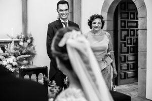 Boda en Villaviciosa de Carmen y David realizada por el fotógrafo de bodas en Asturias Johnny García. El novio sonríe al ver a la novia entrando a la iglesia.