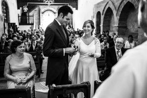 Boda en Villaviciosa de Carmen y David realizada por el fotógrafo de bodas en Asturias Johnny García. El novio le pone el anillo a la novia delante del sacerdote.