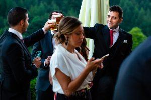 Boda en Villaviciosa de Carmen y David realizada por el fotógrafo de bodas en Asturias Johnny García. Amigos de la pareja brindan con cerveza.