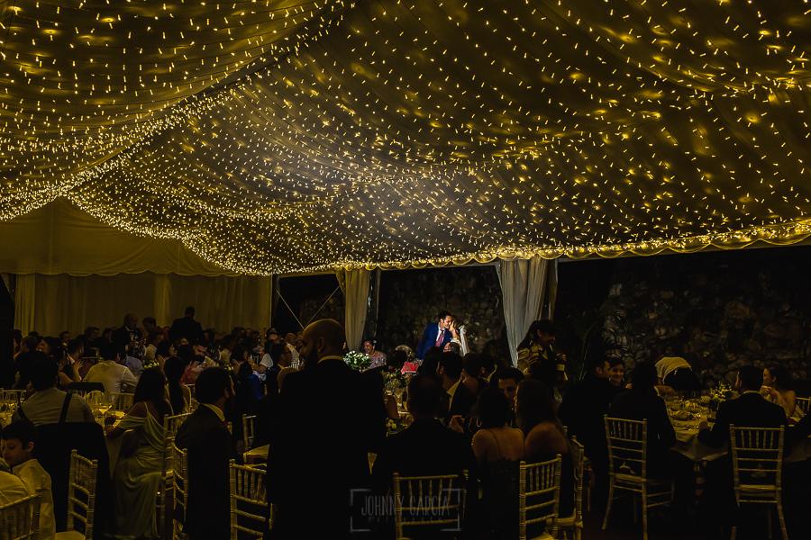 Boda en Villaviciosa de Carmen y David realizada por el fotógrafo de bodas en Asturias Johnny García. Los novios se besan en la mesa nupcial.