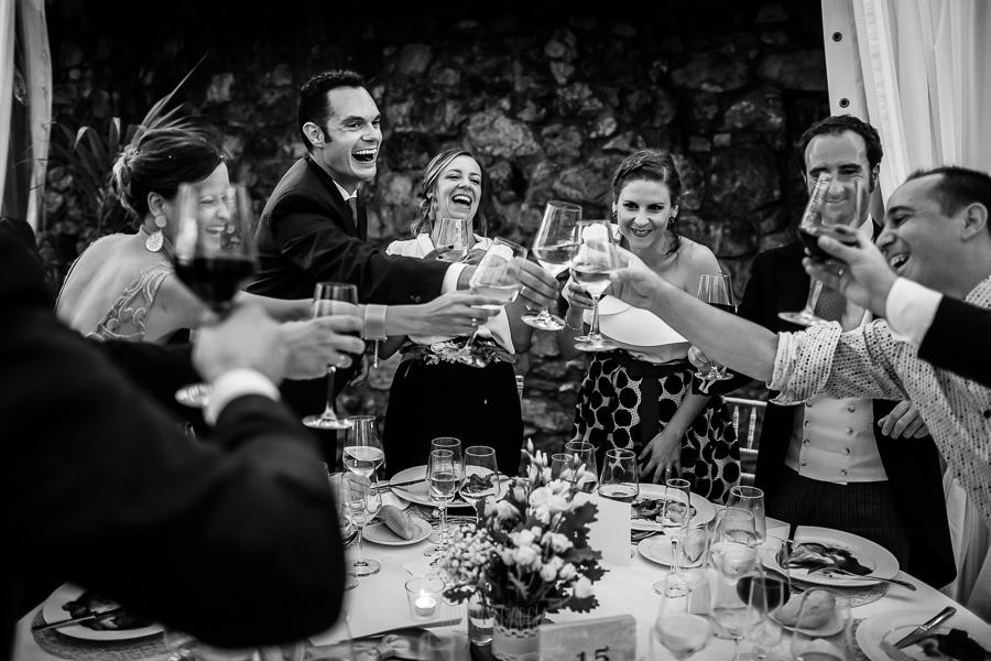 Boda en Villaviciosa de Carmen y David realizada por el fotógrafo de bodas en Asturias Johnny García. Los novio brindan en la mesa de los amigos.