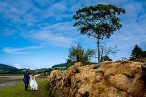 Boda en Villaviciosa de Carmen y David realizada por el fotógrafo de bodas en Asturias Johnny García. Foto de postboda en la ría con la pareja de espaldas.