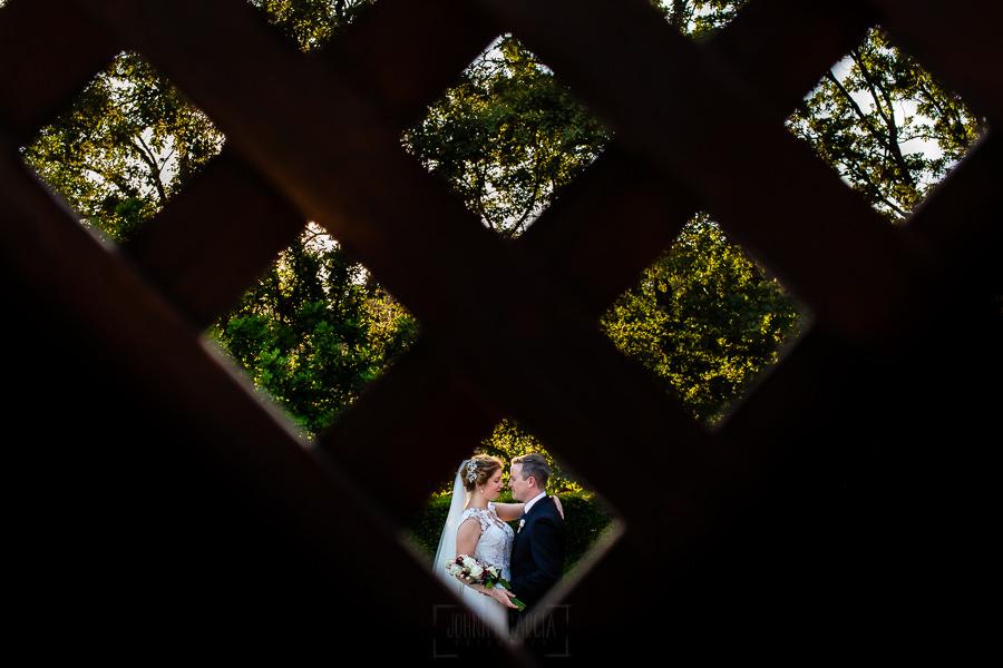Bodas Jarandilla de la Vera, boda de Clara y David en el Hotel Ruta Imperial, fotos realizadas por Johnny García, fotógrafo de bodas en Cáceres. La pareja vista por el hueco de una valla.