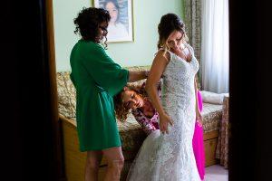 Boda en Aldeanueva del Camino de Sonia y Samuel realizada por el fotógrafo de bodas Johnny García. La madre de Sonia la ayuda a vestirse.
