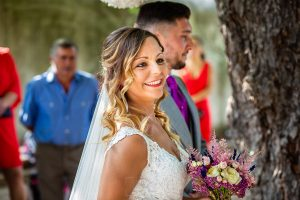 Boda en Aldeanueva del Camino de Sonia y Samuel realizada por el fotógrafo de bodas Johnny García. Sonia sonríe a sus familiares y amigos.