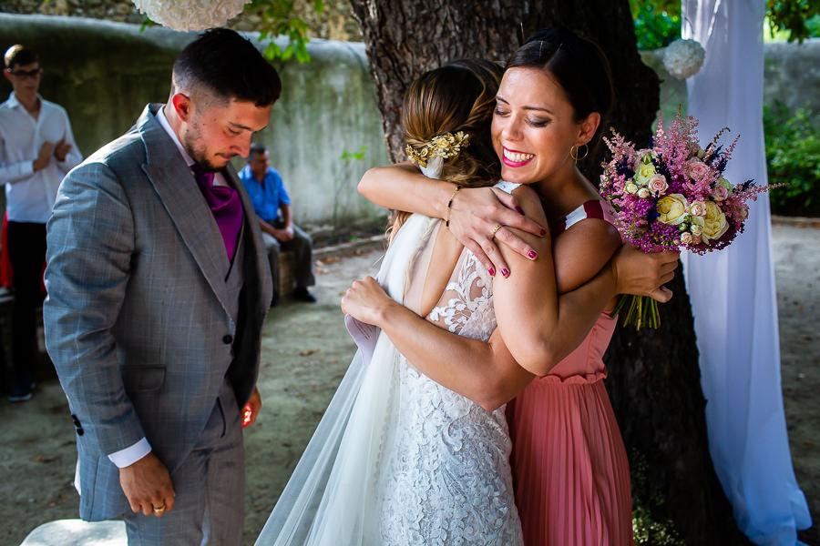 Boda en Aldeanueva del Camino de Sonia y Samuel realizada por el fotógrafo de bodas Johnny García. Sonia abraza a su prima.