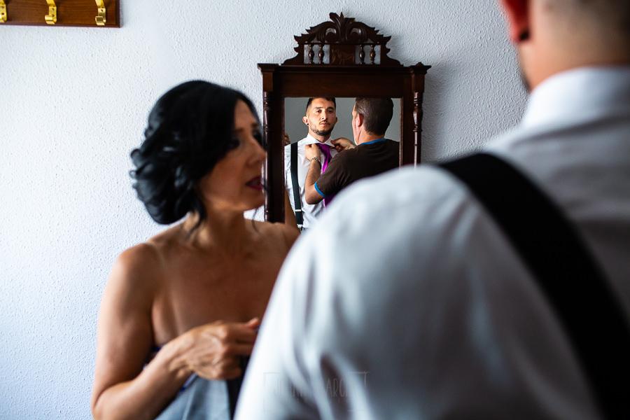 Boda en Aldeanueva del Camino de Sonia y Samuel realizada por el fotógrafo de bodas Johnny García. Los padres de Samuel le ayudan a vestirse.
